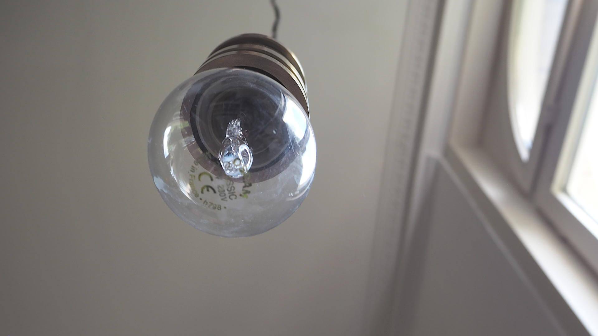 Wach werden mit Licht - Glühbirne, die von der Decke hängt