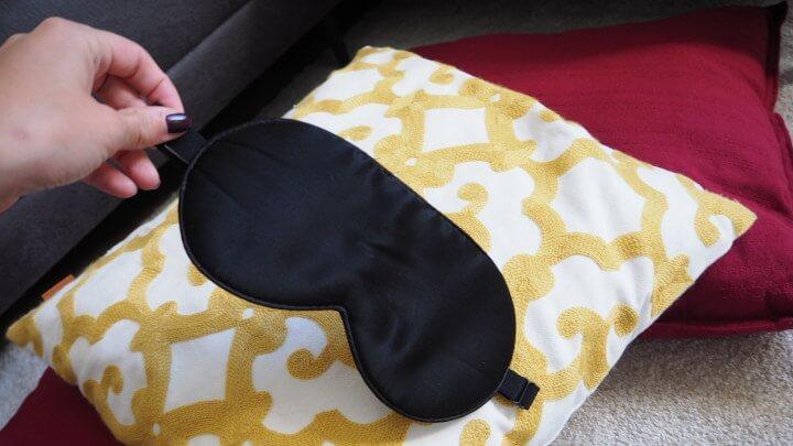 Schlafmaske auf verziertem Kissen